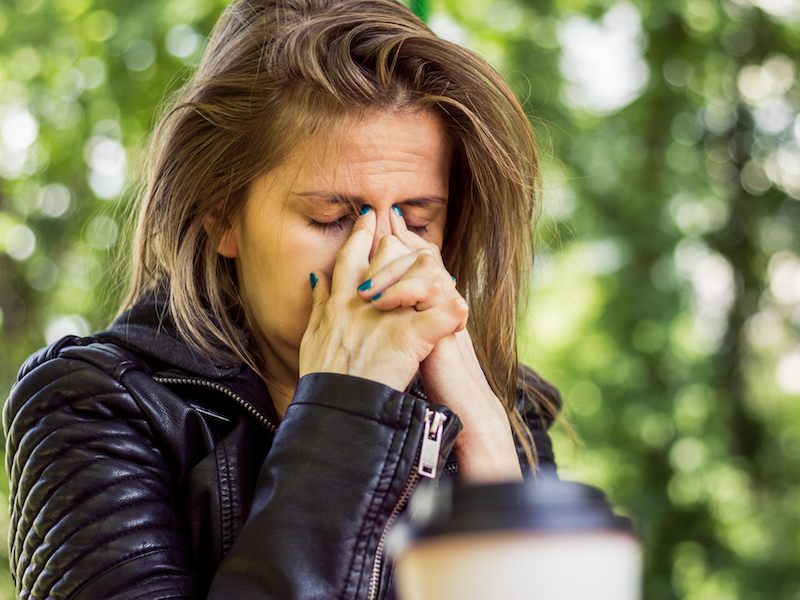 Woman with a sinus infection rubbing her face.