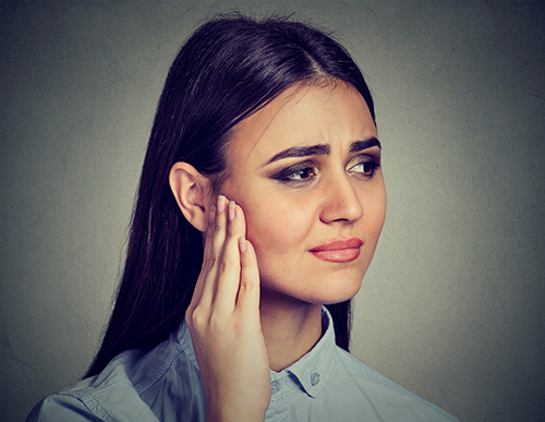 Tinnitus Retraining Therapy | Woman Holding Her Ear in Pain