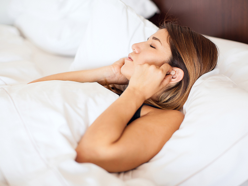 Picture of woman using ear plugs at night