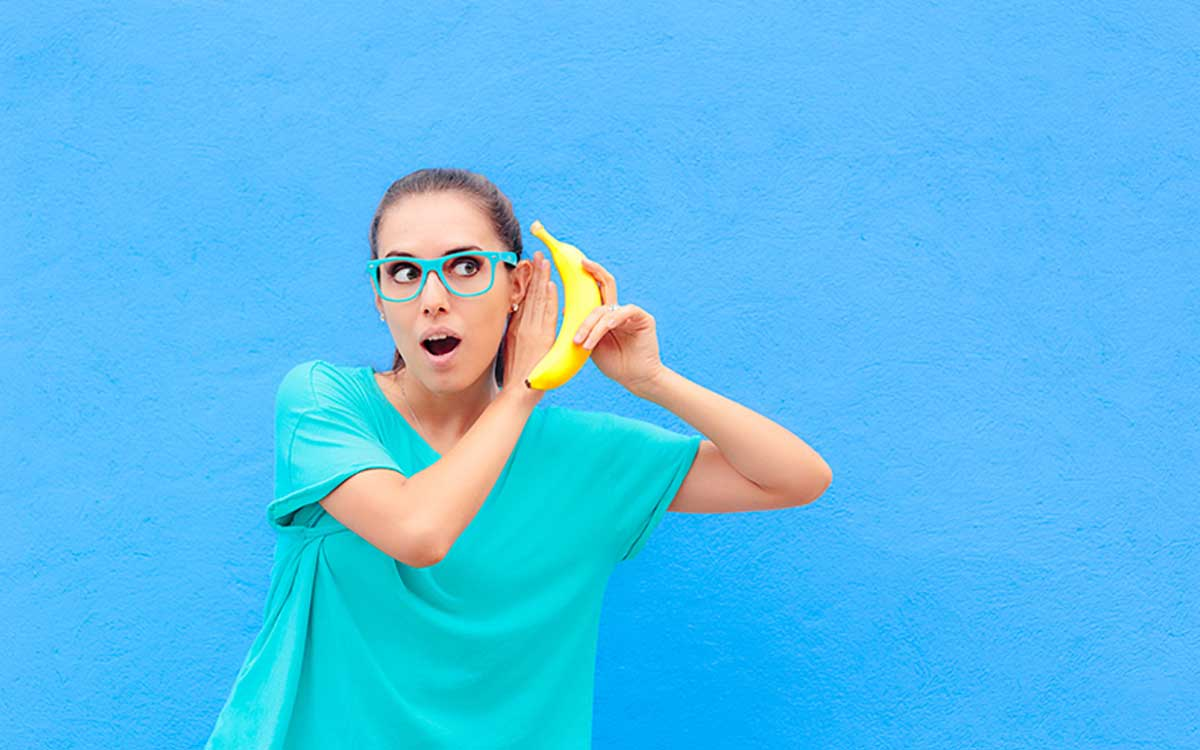 Woman with a banana up to her ear