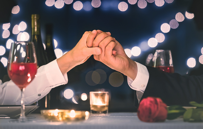 Couple holding hands at Valentine's Day dinner.
