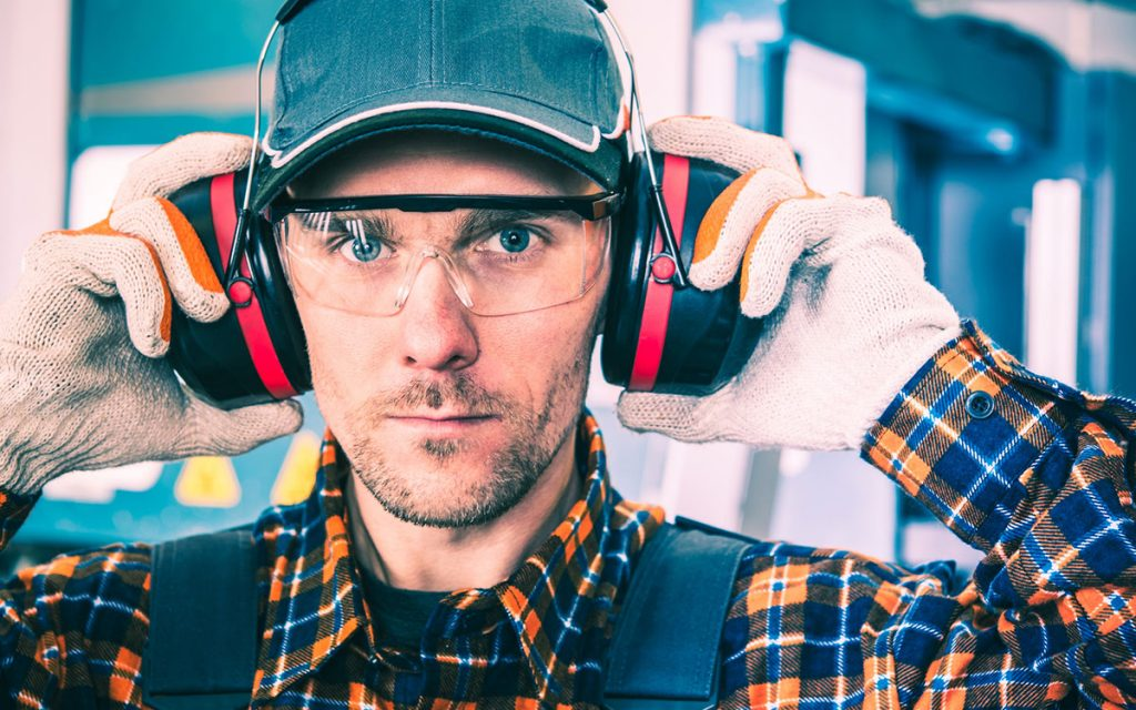 Man protects his hearing with earmuffs with bluetooth and radio capabilities.