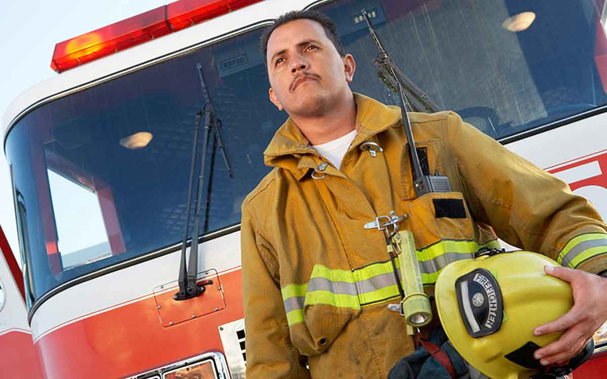 Firefighter in front of a firetruck.