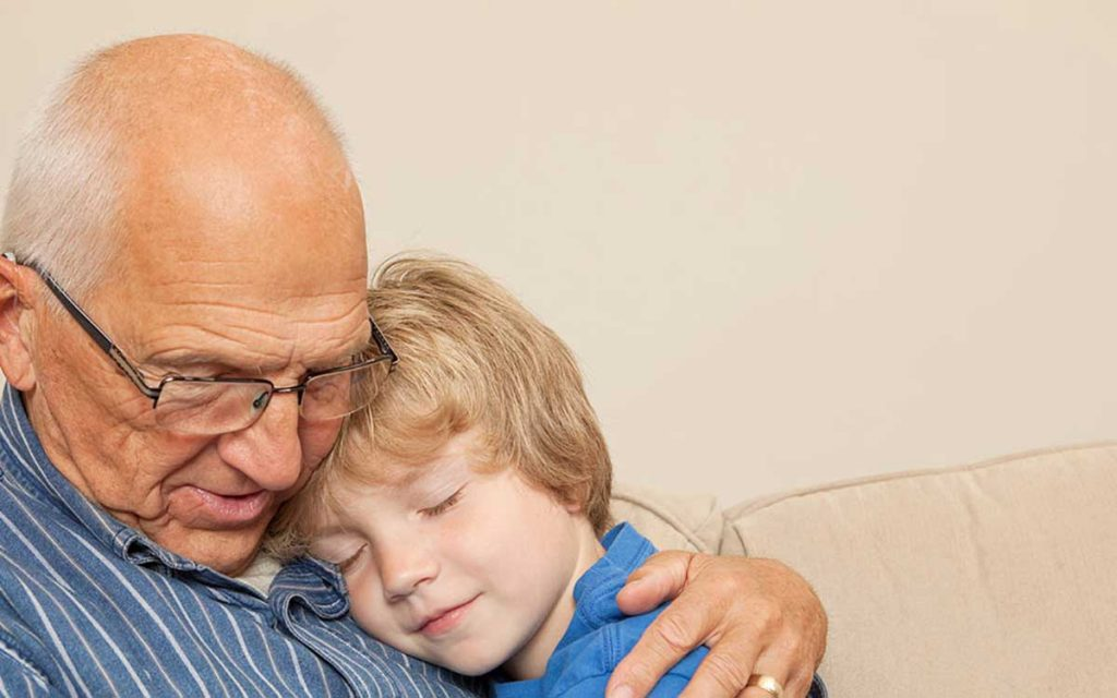 A grandfather who is wearing hearing aids.