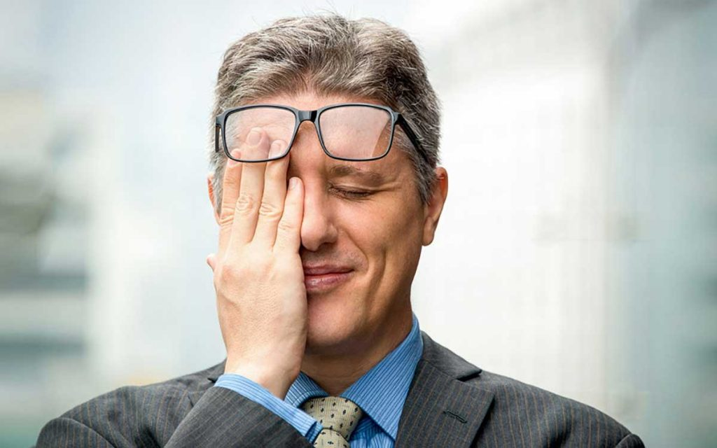 Man with his hands on his face. Made a mistake with hearing aids.