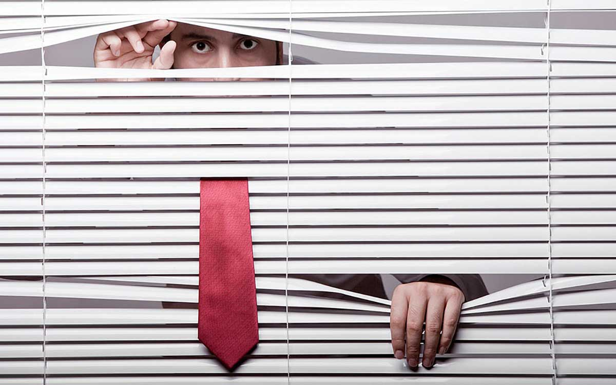 Man peeping through blinds because he is hiding.