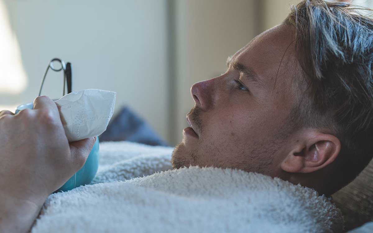 Man sick in bed from hearing loss.