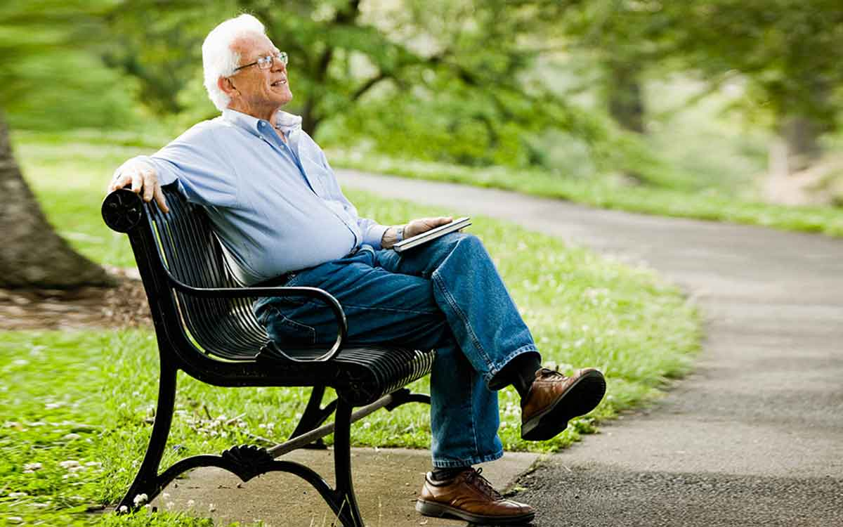 Man relaxing on park bench and worry free with a hearing aid guide.