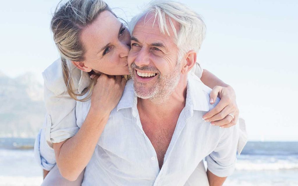 Middle aged happy couple looking young despite hearing loss.