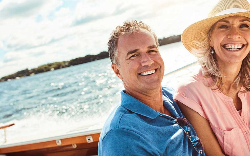 Happy couple on boat discovering the benefits of hearing aids.