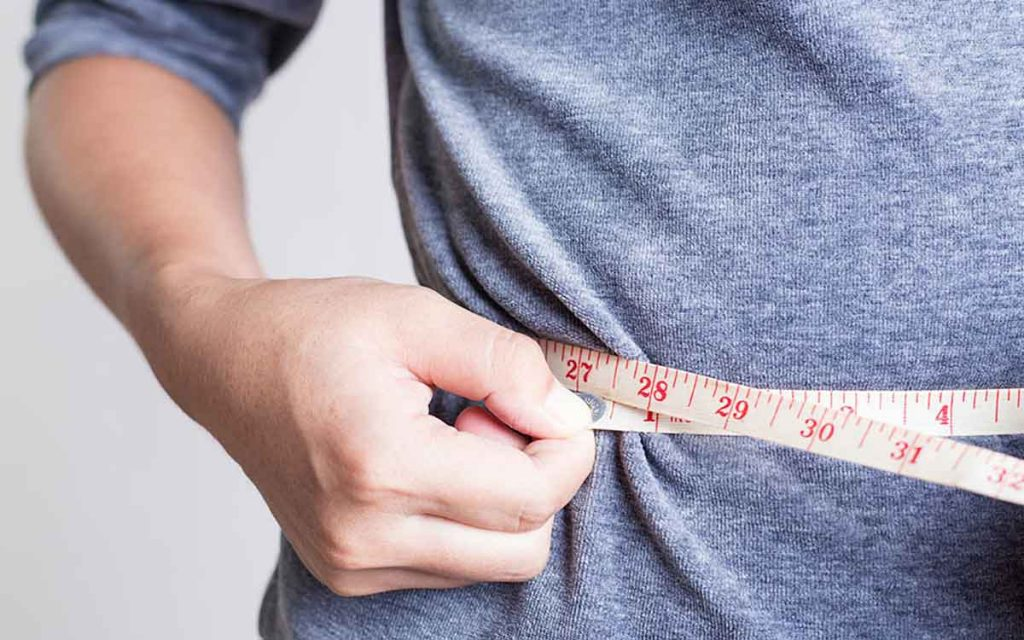 Man with a measuring tape around waist. How does your weight affect your hearing?