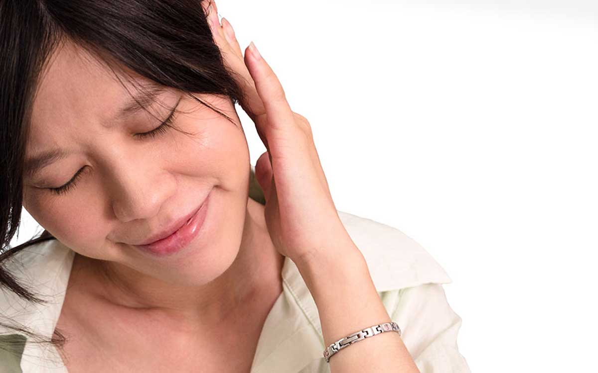 Woman with hand to her ear, suffering from Tinnitus and ringing in her ear.