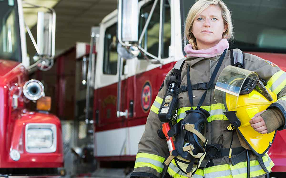 Woman firefighter in front of a fire station. Hearing loss can come from firetrucks.