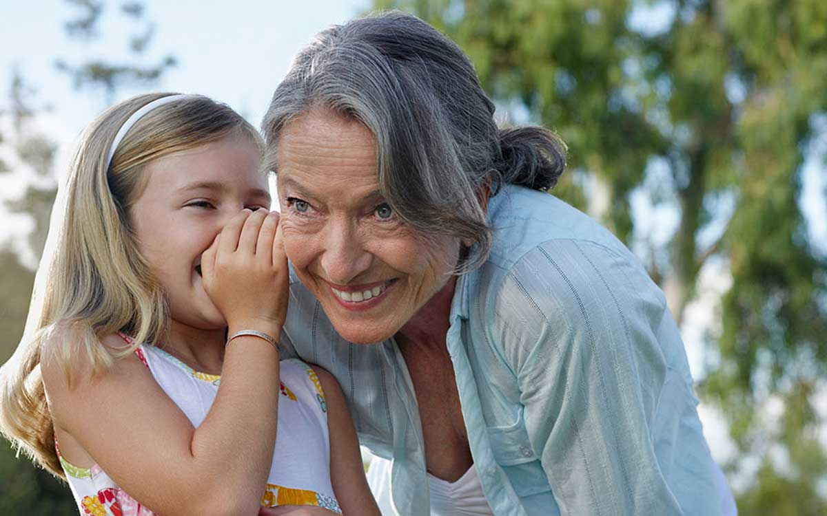 Grand daughter whispering into grandmother's ear. Single sided deafness treatments.