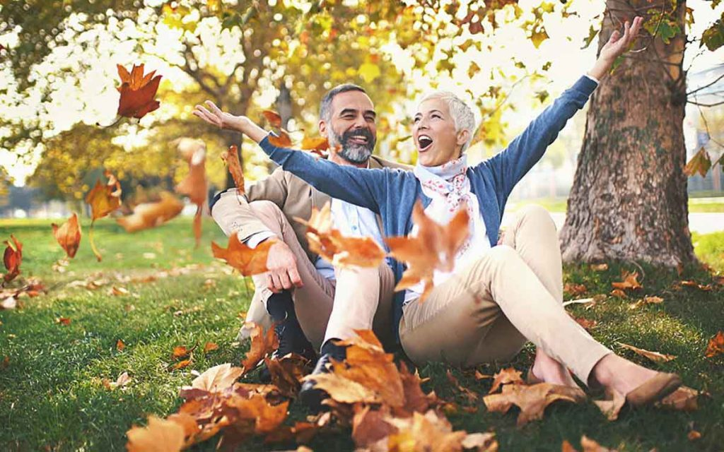 Happy couple playing in the leaves.