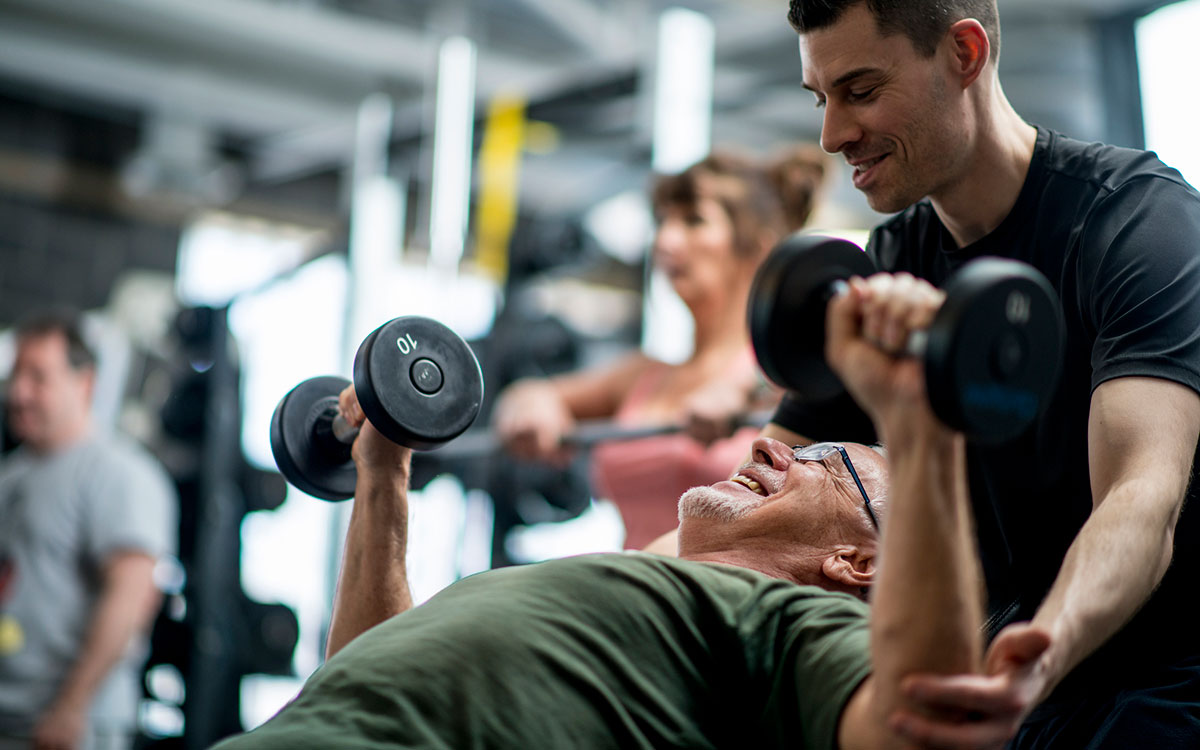 Trainer helping man avoid workout -related hearing loss with proper position of weights.