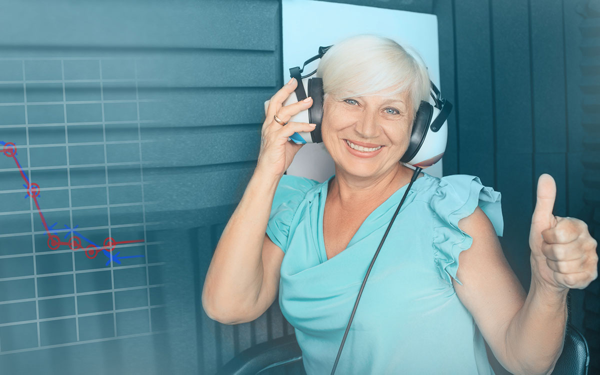 Woman with headphones on in from of a an Audiogram printout.