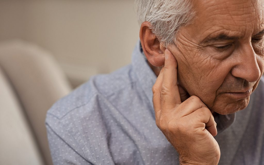 Man with his hands to ear suffering from Tinnitus.