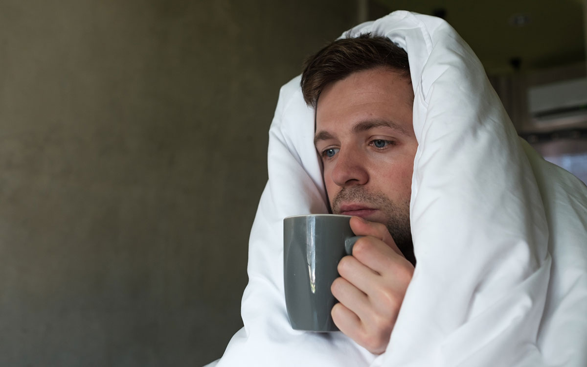Man suffering from a cold and possibly suffering from hearing loss.
