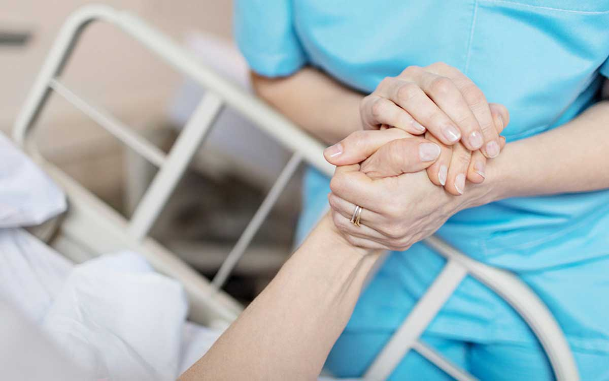 Woman holding hands of person who is in the hospital because of hearing loss.