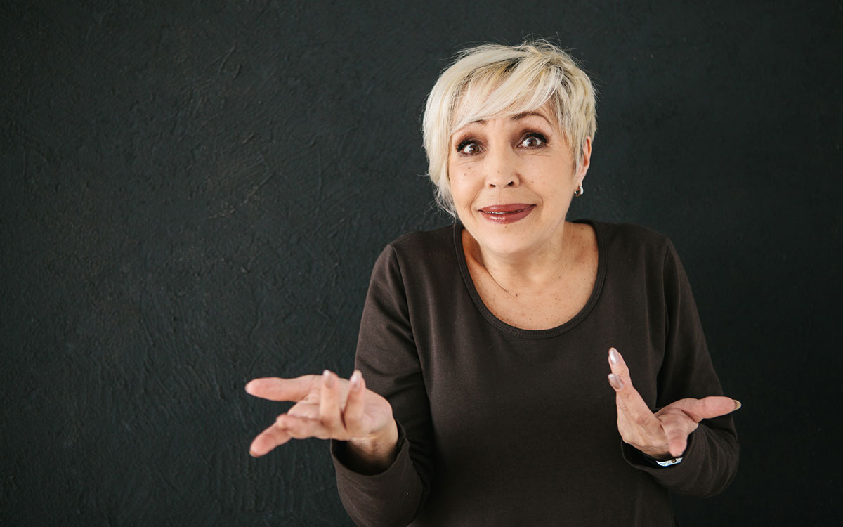 Woman shrugging her shoulders with questions about hearing aids.