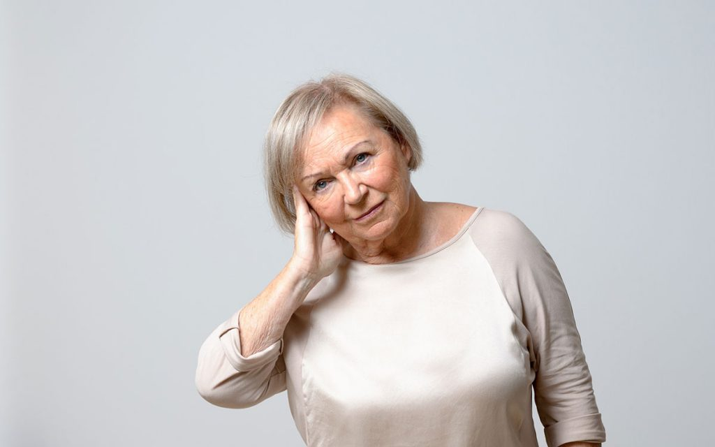 Woman suffering from Tinnitus who is considering hearing aids.