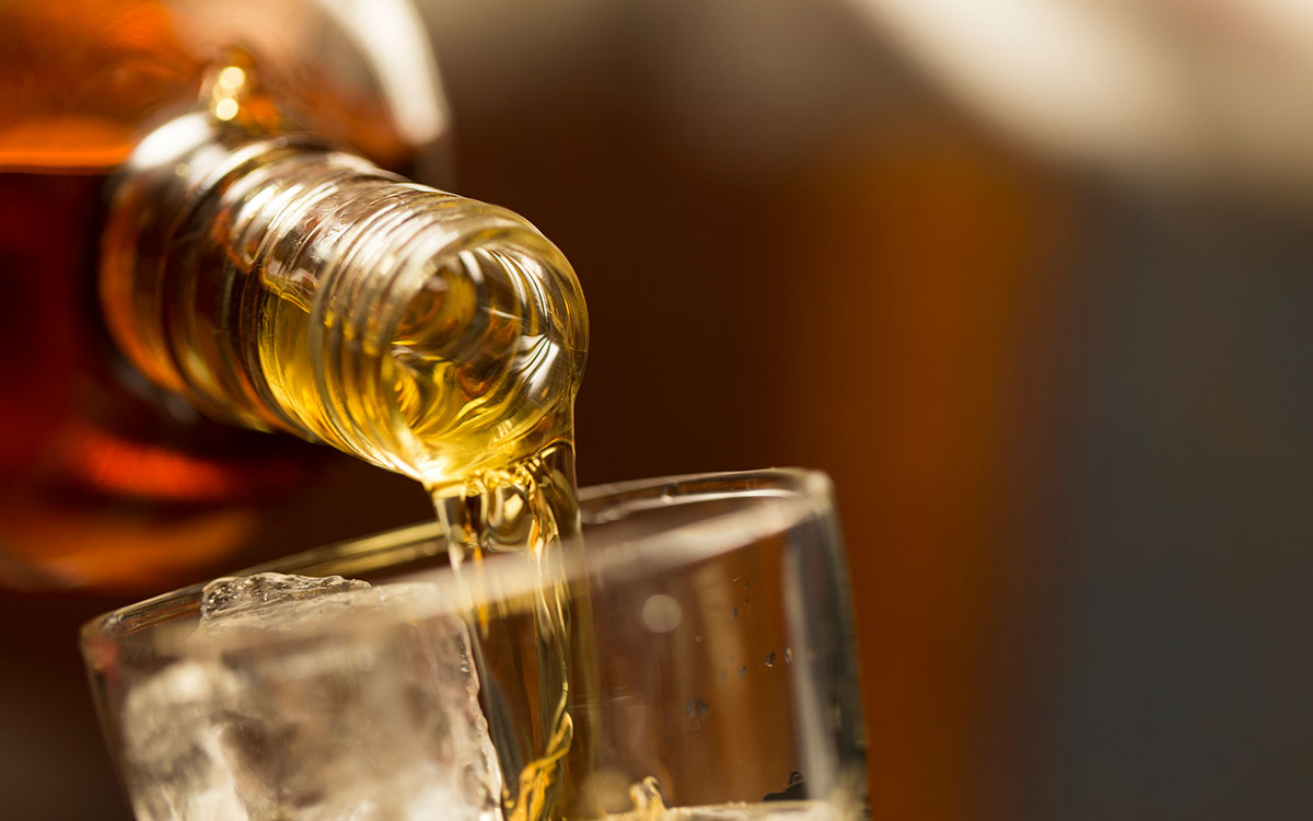Alcohol pouring from a bottle contributing to hearing loss.