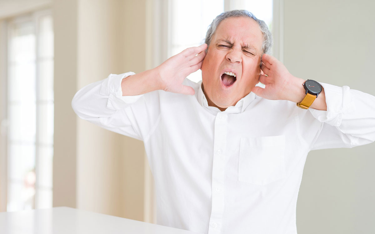 Man with hands on his ears because of hissing and buzzing hearing aids.