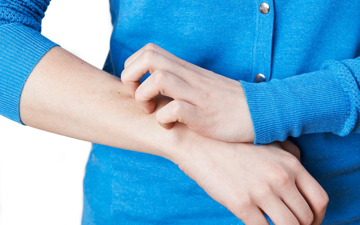 Woman scratching her arm because of psoriasis. Hearing loss linked to psoriasis.