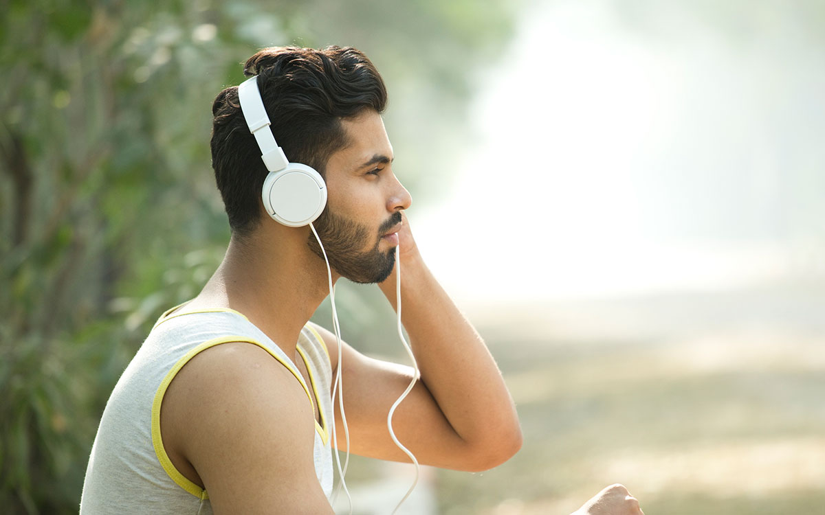 Twenty year old that is wearing headphones and suffering from hearing loss.