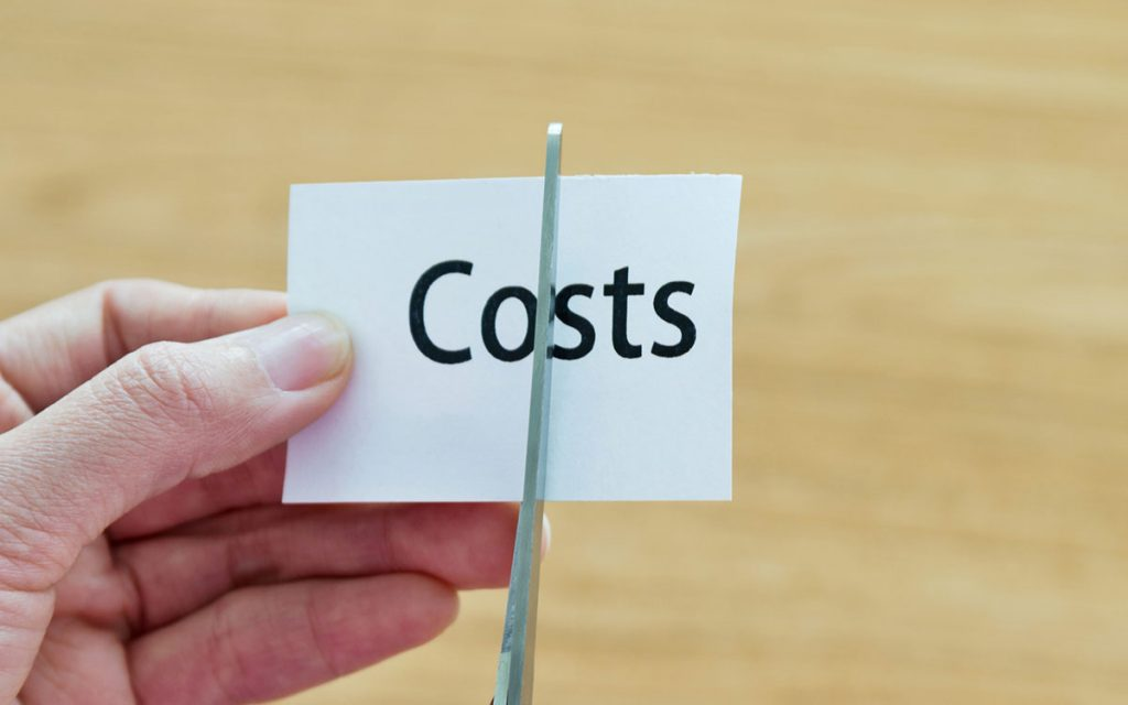 Scissors cutting through paper called costs.