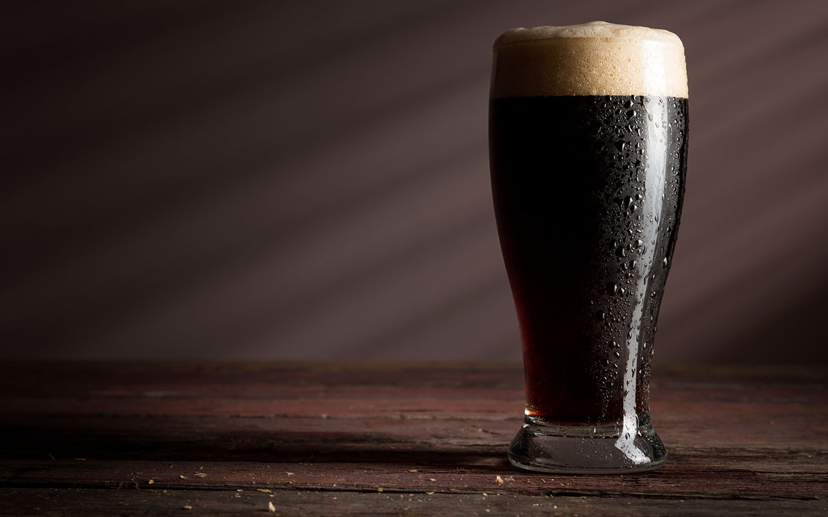 Glass of dark beer which may help with hearing loss.