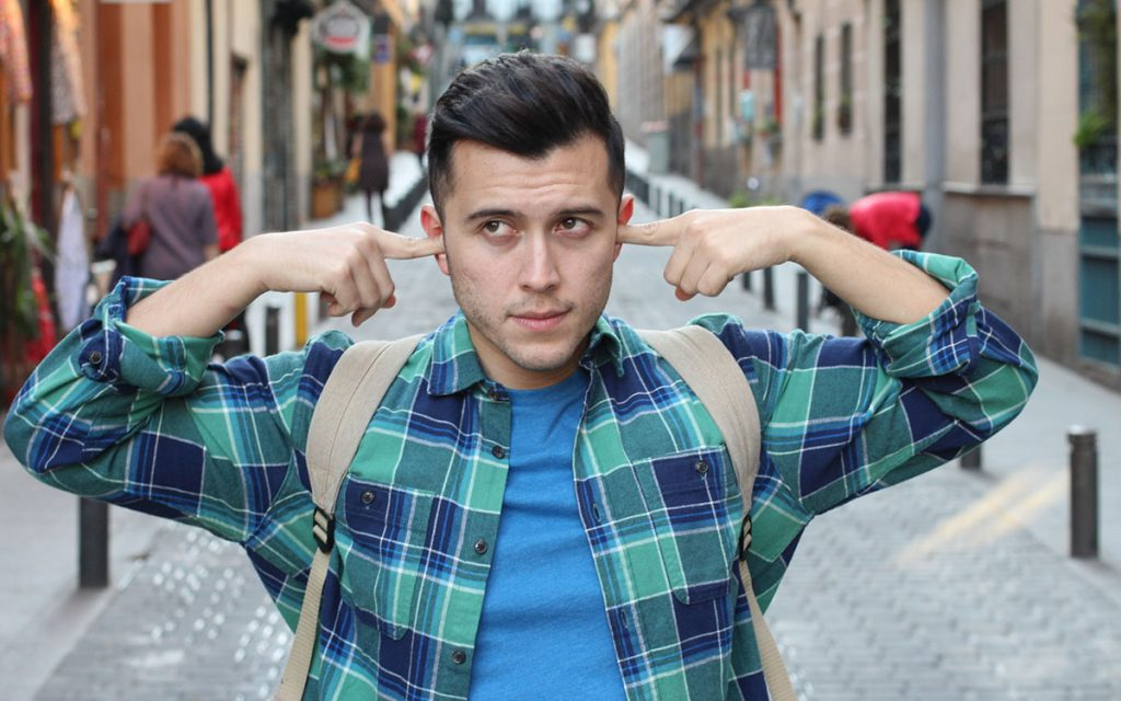 Man holding his ear because of noise pollution.