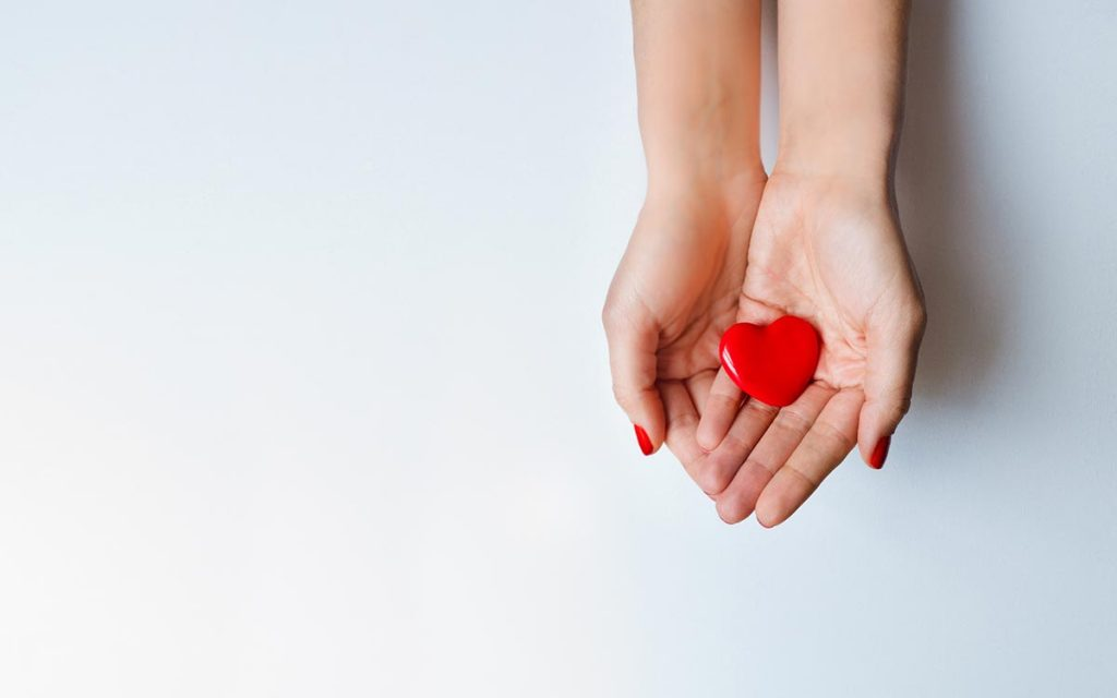 Hands holding a heart representing the benefits of hearing aids.
