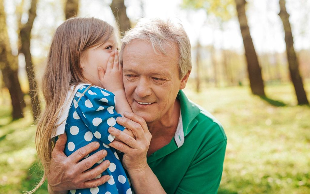 Man with granddaughter whispering into his ear. Comfortable hearing aids.