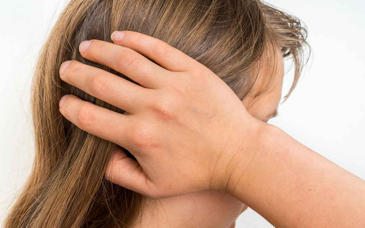Woman holding her head because her environment is causing Tinnitus.