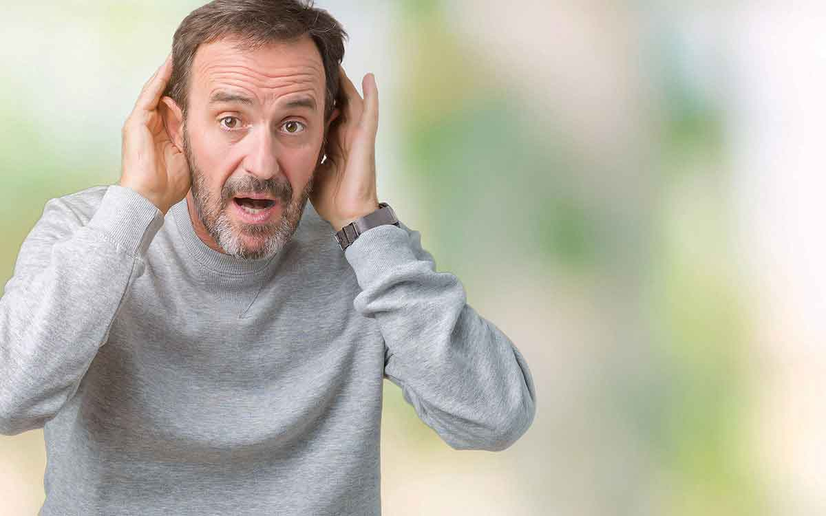 Man with hands to his hears . Conductive hearing loss factors.
