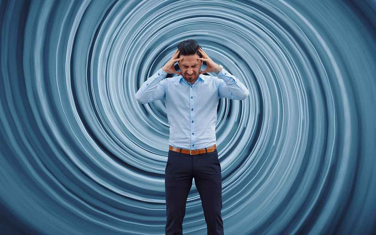 Man with dizzy swirl behind him suffering from hearing loss.