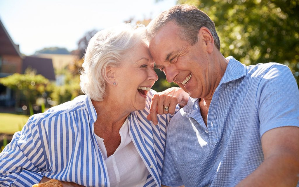 Happy senior couple seeing a hearing specialist.