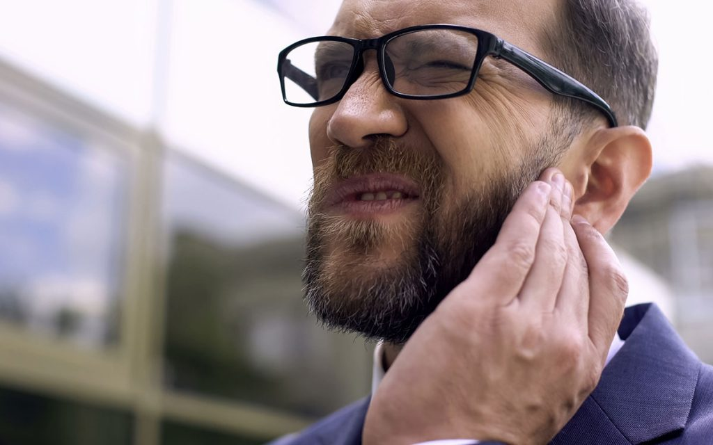 Man holding his ear because earwax is giving him hearing loss.