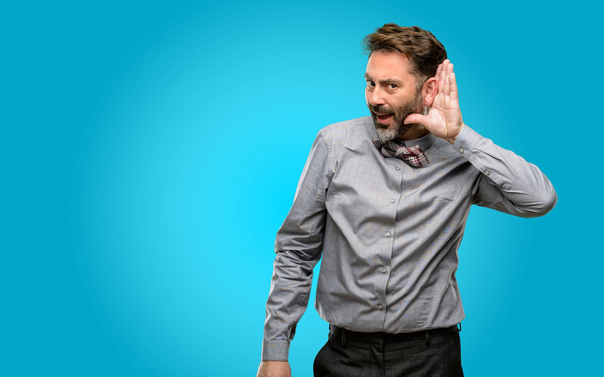 Man with his hand to his ear because he cannot hear even with hearing aids.