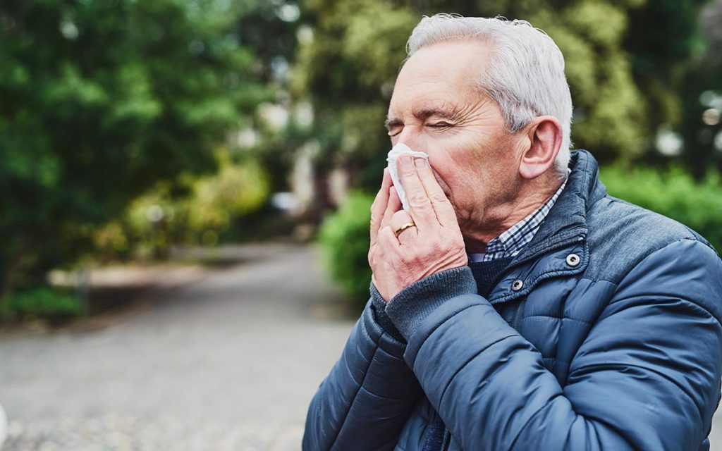 Man blowing his nose because of sinus infection.