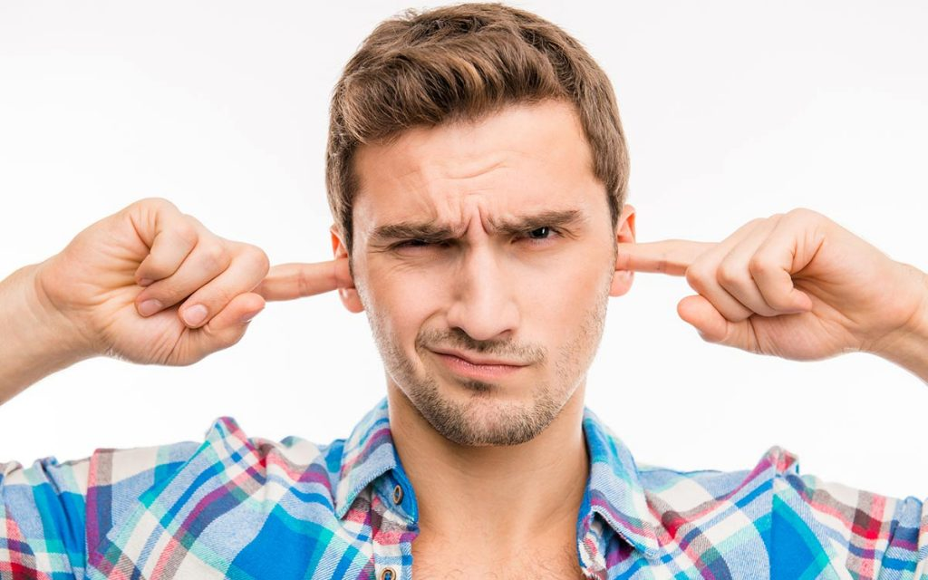 Man with his fingers in his ears symbolizing hearing protection.