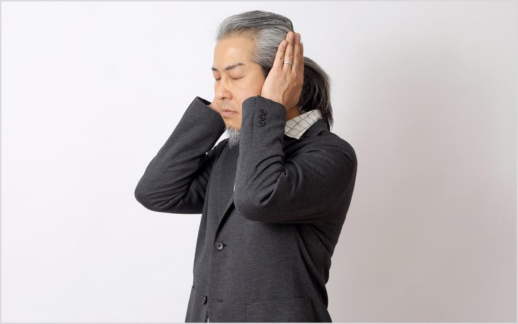 Man with his hand over his ear suffering from Tinnitus and hearing his heartbeat.