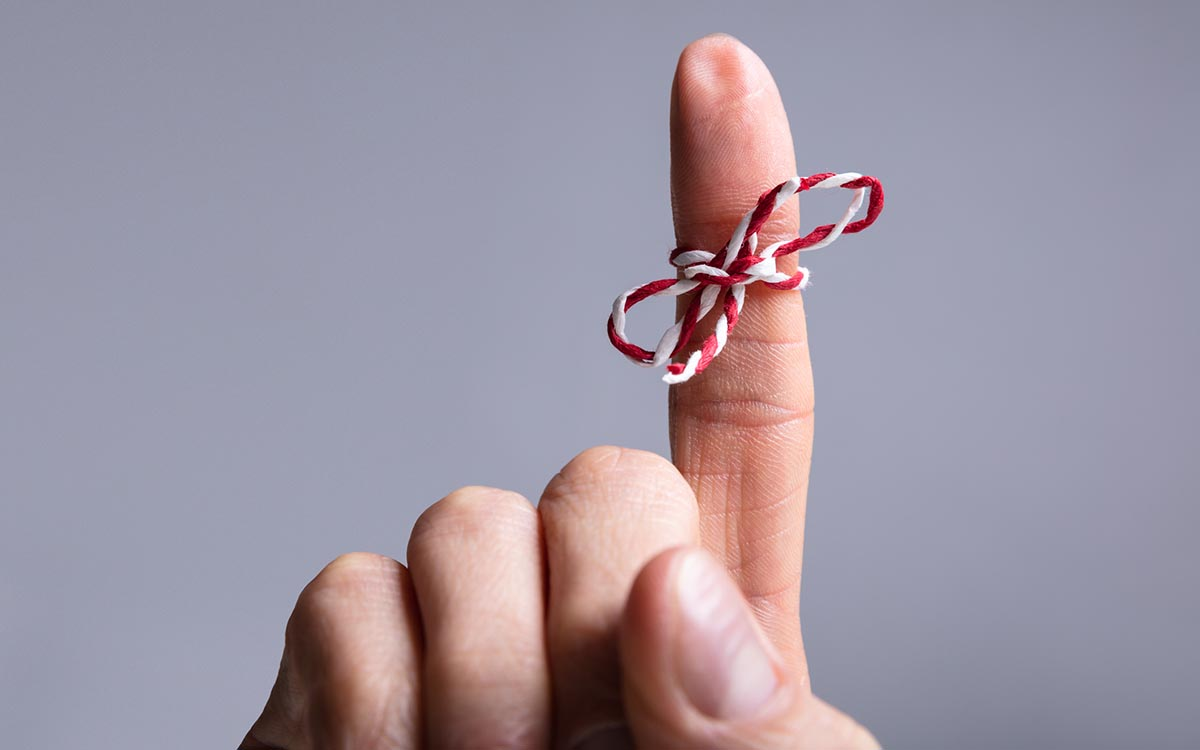 Finger with string tied around it representing hearing loss and memory loss.