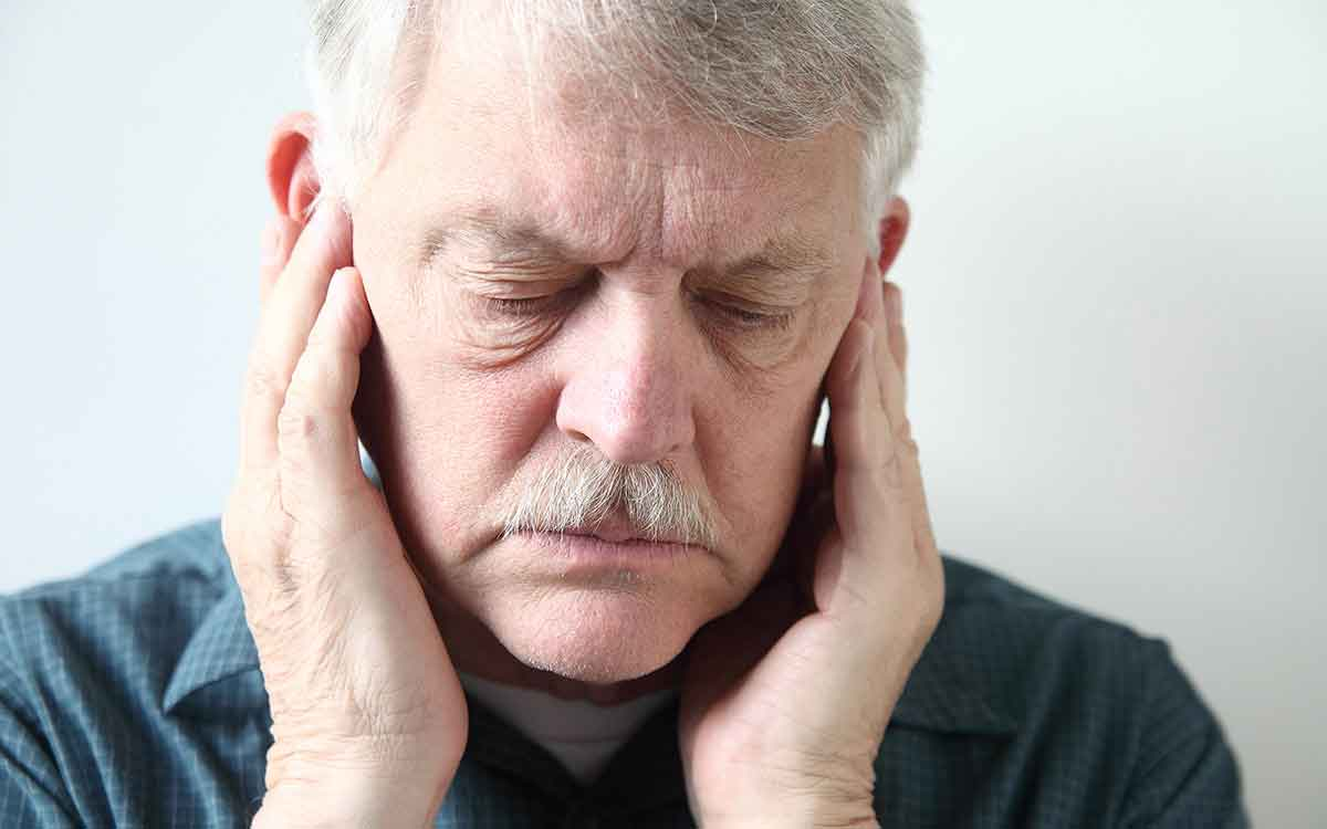 Man with his hands over his ears suffering from Tinnitus.