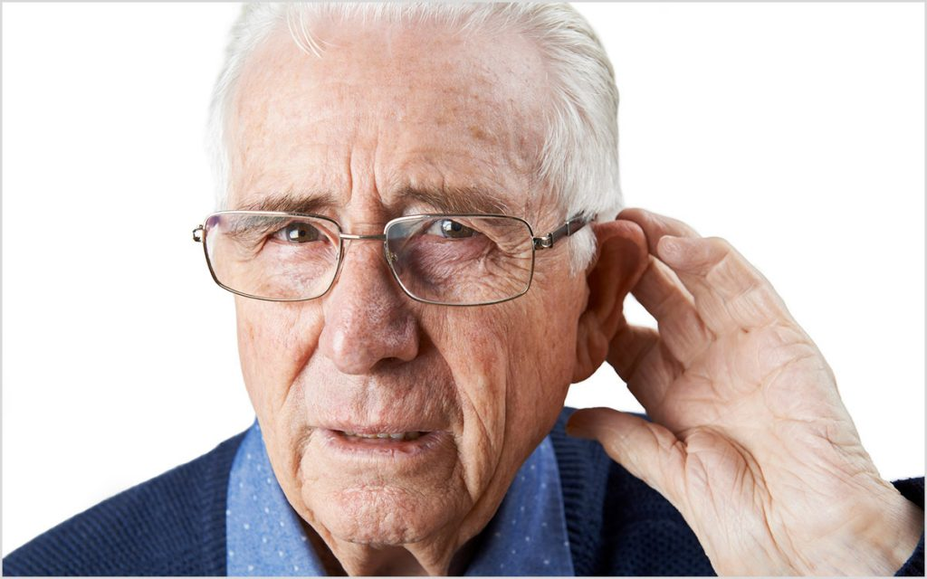 Man with his hand up to his ear wondering what Tinnitus sounds like.