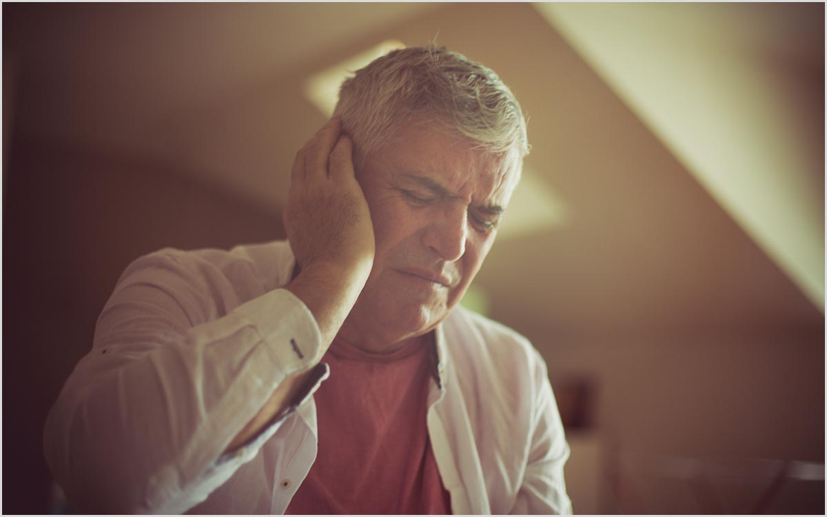Man with his hands on ear because of Tinnitus.