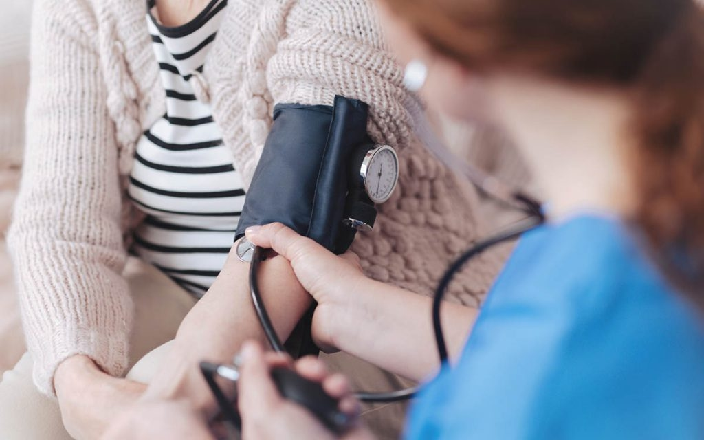 Woman getting her blood pressure taken. Associated diseases related to hearing loss.