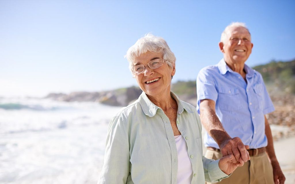 Shot of a happy elderly couple on the beach suffering from hearin gloss.